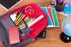 Ryggsäck med sortimentet av skolatillförsel royaltyfri fotografi