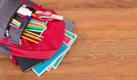 Ryggsäck med sortimentet av skolatillförsel arkivfoton