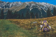 Ryggsäck och gå pinnar på bergslinga royaltyfria bilder