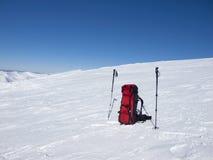 Ryggsäck och trekking poler i snön fotografering för bildbyråer