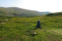 Ryggsäck på ängen med berg på bakgrunden Sommar som fotvandrar motivational bild Utrymme f royaltyfria bilder