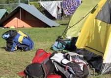 Ryggsäckar av fotvandrare i mitt av campa tält Royaltyfri Fotografi