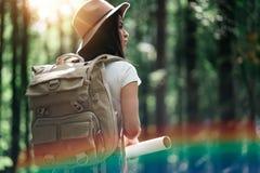 Ryggsäcken och hatten för eftertänksam gullig handelsresandekvinna rymmer den bärande lägeöversikten i händer bland träd på solne royaltyfria foton