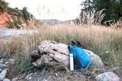 Ryggsäcken och termos är nära stenen arkivfoto