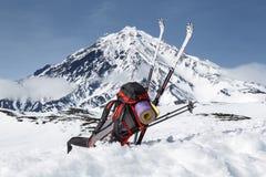 Ryggsäcken skidar, och poler ligger på snön på bakgrundsvulkan Royaltyfri Foto