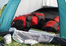 Ryggsäckar i tältet och en aluminum lunchbox Arkivbilder