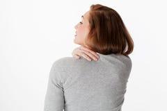 Ryggvärkbegrepp, 20-talkvinna i tillbaka sikt med skuldror och halsspänning Royaltyfri Foto