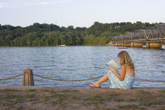Ryley reading. Young girl reading by the water and bridge Royalty Free Stock Images
