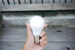 Rym den ljusa LEDDE kulan i hand med träbänkbakgrund Royaltyfria Foton