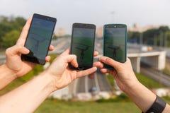 Rymda telefoner för träd går vännen i en hand som visar dess skärm med Pokemon, applikationen Fotografering för Bildbyråer