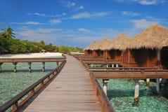Rymlig Overwater bungalow med den långa trägångbanan Arkivbilder