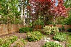 Rymlig trädgård med staketet Royaltyfri Foto