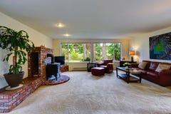 Rymlig vardagsrum med klippning och ugnen för tegelstenvägg Arkivfoton
