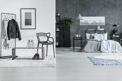 Rymligt grått sovrum med filtar arkivfoton