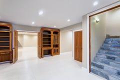 Rymligt tomt källareområde med specialbyggda bokhyllor arkivfoton