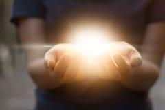 Rymma öppnar händer med glödande ljus på mörk bakgrund arkivfoton