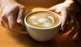 Rymma en kopp kaffe med tv? h?nder royaltyfri bild