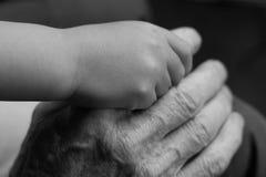 Rymma för unga och gamla händer Arkivfoto