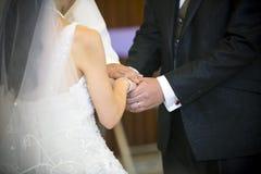 Rymma händerna tillsammans i bröllopceremoni Arkivfoto