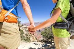 Rymma romantiska par för händer som fotvandrar Grand Canyon Arkivfoto