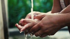 Rymmande och tvättande dotterhand för kvinna under en vattenkran lager videofilmer