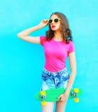 Rymmer den nätta kvinnan för mode skateboarden över färgrika blått arkivbild