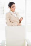 Rynka pannan affärskvinnaanseende bak hennes stol som rymmer hennes telefon som att glo på kameran royaltyfri bild