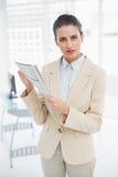 Rynka pannan den smarta bruna haired affärskvinnan som rymmer en tidning royaltyfri fotografi