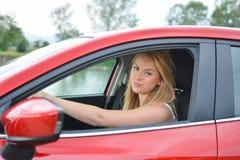 Rynka pannan den unga blonda flickan i röd bil royaltyfri bild