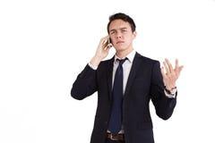 Rynka pannan den unga Caucasian affärsmannen som rymmer en mobiltelefon Fotografering för Bildbyråer