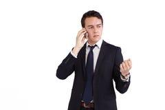 Rynka pannan den unga Caucasian affärsmannen som rymmer en mobiltelefon Arkivbild
