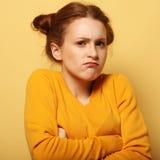 Rynka pannan den unga kvinnan som tänker på gul bakgrund arkivbilder
