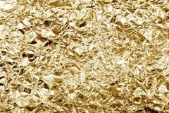 Rynkigt skinande gult guld- dekorativt texturpapper för färg Skrynkligt metallmaterial för guld- folie för hantverkdesigngarnerin royaltyfri foto