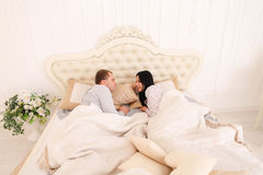 RYoung couple talking and wife resents husband lying in bed Stock Photography