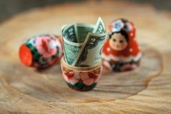 Rysk docka med dollar inom Anti-krissparbössa arkivbild