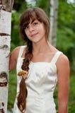 Rysk flicka i den vita klänningen i en björkskog Royaltyfria Bilder