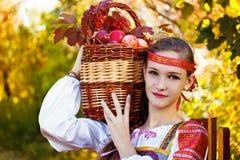 Rysk flicka i en dräkt som rymmer en korg av äppleskörden Arkivbild