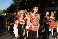 Rysk grupp av dansare i traditionella dräkter på den internationella folklorefestivalen för barn och guld- fisk för ungdom Royaltyfria Bilder