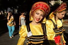 Rysk grupp av dansare i traditionella dräkter på den internationella folklorefestivalen för barn och guld- fisk för ungdom Arkivfoto