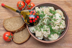 Rysk kokkonst: klimpar på en platta, körsbärsröda tomater och ett bröd Royaltyfri Foto