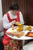Rysk kvinna som målar en matryoshka på biten 2014, internationellt turismutbyte i Milan, Italien royaltyfria bilder