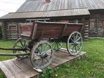 Rysk lantlig bondaktig vagn för antik tappning i gården av ett trähus Royaltyfri Fotografi