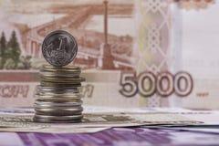Rysk myntkopeck på bakgrunden av rubelsedeln royaltyfri bild