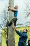 Rysk nationell konkurrens, genom att klättra en träpol i beröm av slutet av vintern i den Kaluga regionen på mars 13, 2016 Royaltyfria Bilder