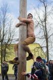 Rysk nationell konkurrens, genom att klättra en träpol i beröm av slutet av vintern i den Kaluga regionen på mars 13, 2016 Royaltyfri Bild