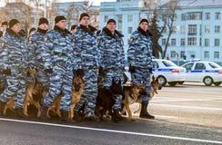 Rysk polisenhet i vinterlikformig med polishundkapplöpning på Kuen Arkivfoto