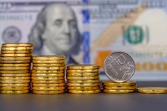 Rysk rubel i myntet som ner rullar på 100 dollar sedelbakgrund royaltyfri bild