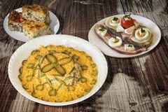 Rysk sallad med baconägget och ostsmörgås- och spenatostpajen Zeljanica på den gamla träträdgårds- tabellen Fotografering för Bildbyråer