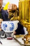 Rysk samovar Hällde det kokande vattnet in i tekannan för br Royaltyfria Foton