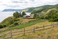 Rysk by Sikt av sjöhuset på lutningen, runt om bergen och skogarna royaltyfria foton